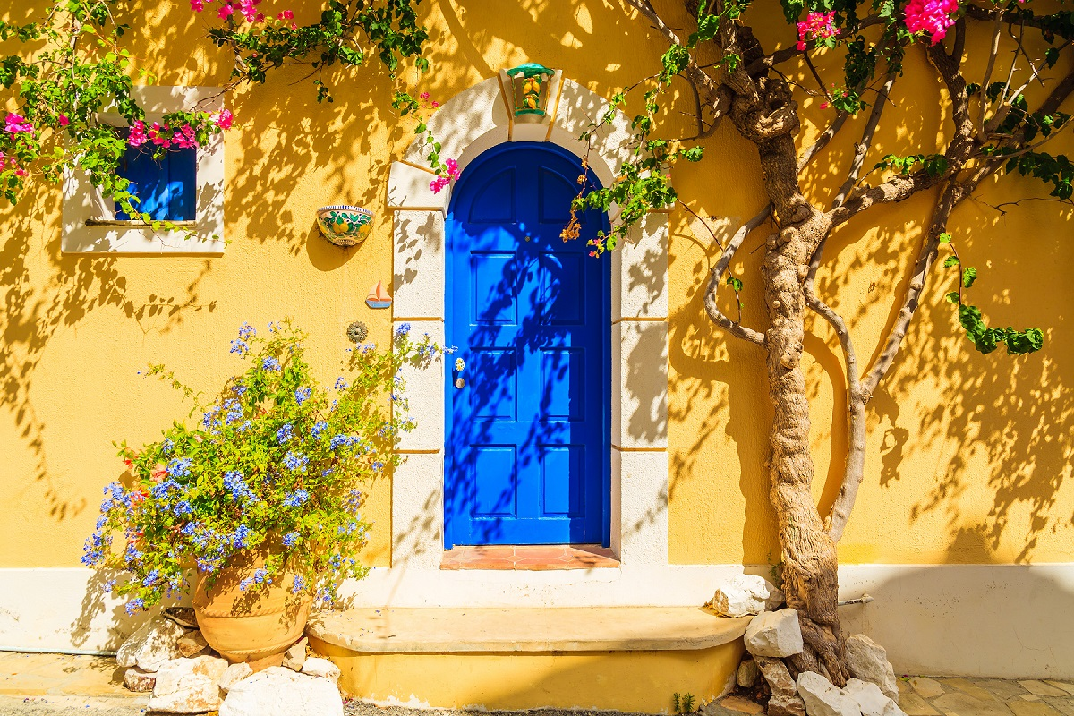Blue door of a yellow Greek house decorated with flowers