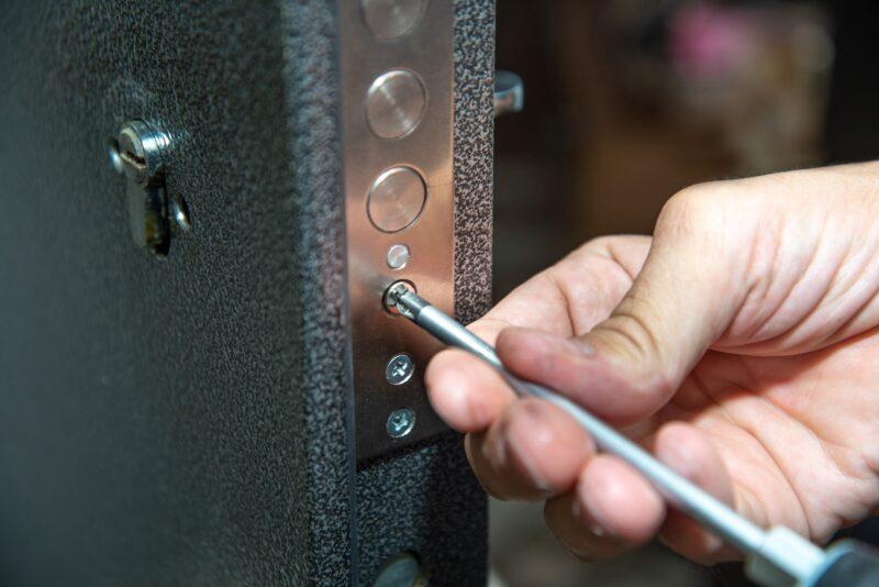 A man repairs a door lock. Close-up